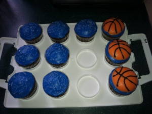 Extra basketball cupcakes and plain frosted cupcakes with white sugar sprinkles on top