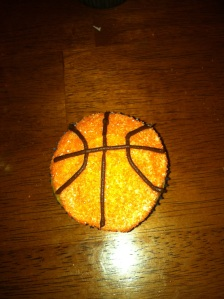 Basketball cupcake with seam lines in chocolate frosting